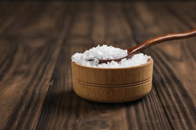 나무 테이블에 굵은 소금을 넣은 나무 컵과 숟가락. 지상 돌 바다 소금.