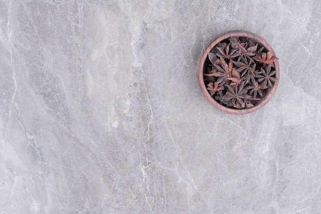 A wooden cup full of anise flowers on the marble