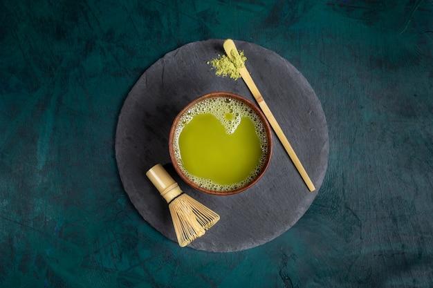 エメラルドの背景にラウンドシェールサービングボードに緑の抹茶と木製のカップ。上面図。