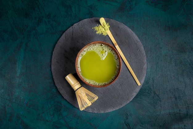 Wooden cup with green matcha tea on round shale serving board on emerald background. top view.