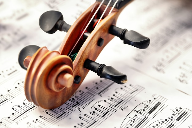 楽譜の上にペグが横たわっているバイオリンの木製のカールがクローズアップ