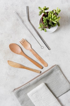 Wooden cutlery on wallet and plant