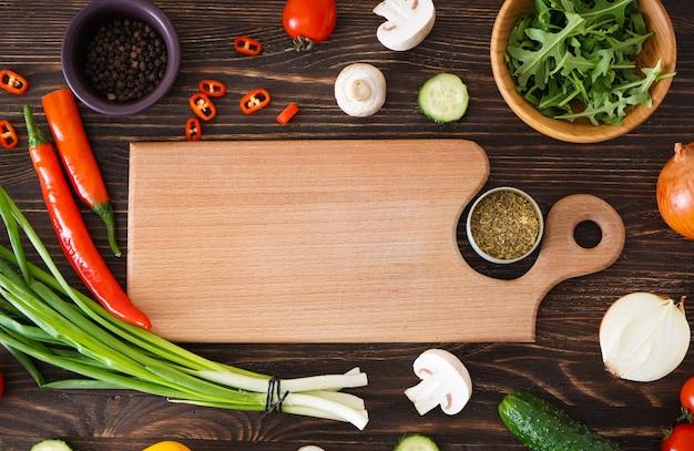 Деревянная разделочная доска и свежие ингредиенты для приготовления пищи на фоне деревянного стола, место для текста. плоская планировка