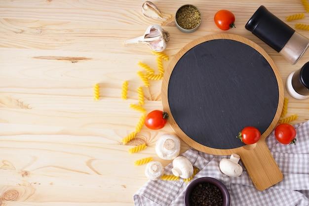 木製のまな板と木製のテーブルの上で調理するための新鮮な食材、テキストのためのスペース。フラットレイ。