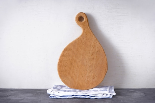 Деревянная разделочная доска и кухонное полотенце на сером фоне, место для текста.