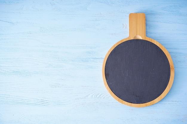 木製のまな板と木製のテーブルの上のキッチンタオル、テキストのための場所。フラットレイ。