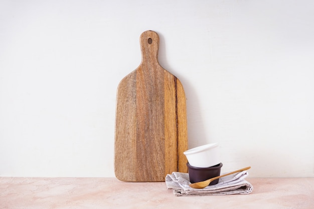 Деревянная разделочная доска и кухонная утварь на бежевом фоне. место для текста