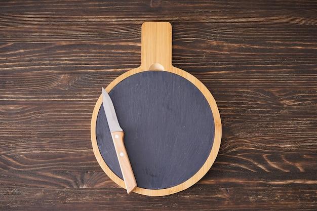 Деревянная разделочная доска и нож на деревянных фоне, место для текста. плоская планировка.
