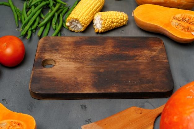 木製のまな板と暗い背景に散らばる野菜をクローズアップ