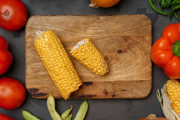 木製のまな板と暗い背景に散らばる野菜