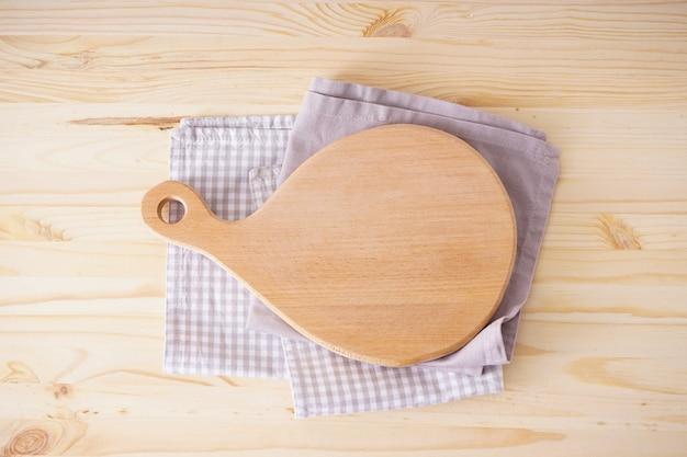 Деревянная разделочная доска и полотенце на деревянных фоне, плоская планировка. место для текста.