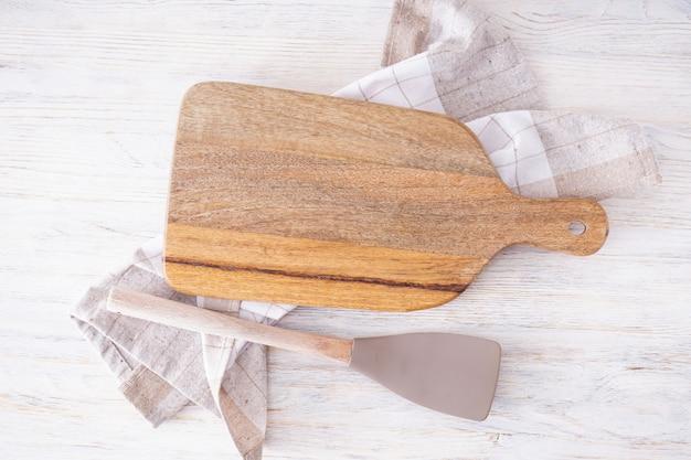 Деревянная разделочная доска и полотенце на деревянных фоне, место для текста. плоская планировка.