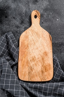 Wooden cutting board. black background. top view. copy space