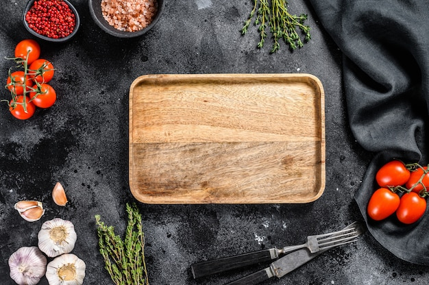 Wooden cutting board  in center of fresh raw greens, vegetables. healthy, clean eating, vegan, dieting food concept. black background. top view. copy space