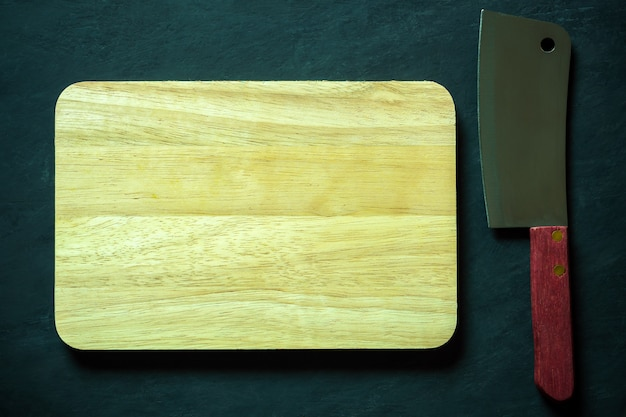 Wooden cutting board and chinese chef knife on black cement floor.