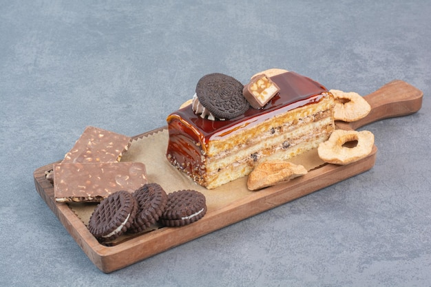 A wooden cutting board of cookies and piece of cake