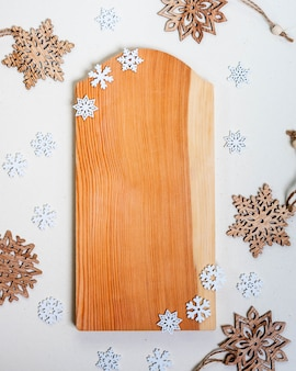 Wooden cutting board frame on white background with snowflakes