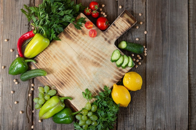 Wooden cutting board next to fresh herbs, raw vgetables and fruits on rustic wooden table