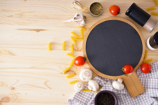 Wooden cutting board and fresh ingredients for cooking over wooden  table, space for text. flat lay.