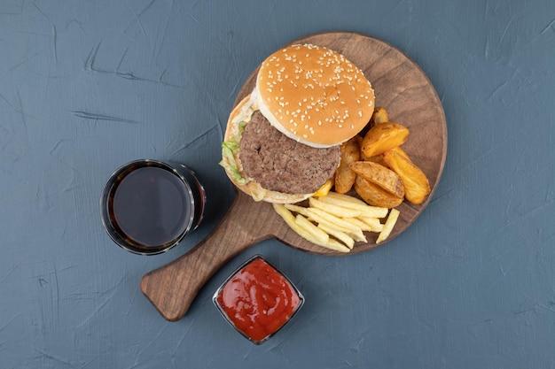 Un tagliere di legno pieno di patate fritte e hamburger.