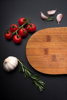 Wooden cutting board and healthy ingredient for cooking on black background