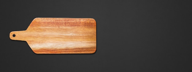 Wooden cutting board isolated on black background. horizontal banner