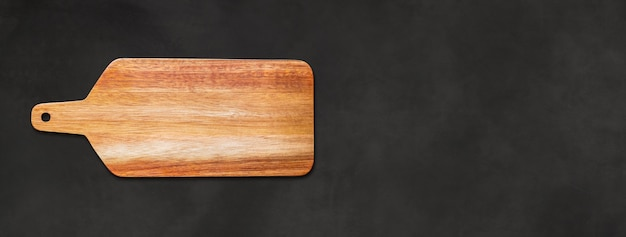 Wooden cutting board isolated on black concrete background. horizontal panoramic banner