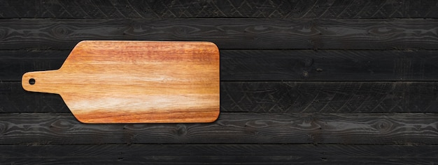 Wooden cutting board isolated on black wood background. horizontal panoramic banner