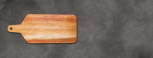 Wooden cutting board isolated on dark concrete background. horizontal panoramic banner