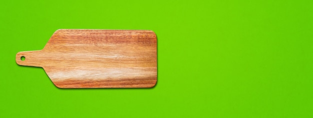 Wooden cutting board isolated on green background. horizontal banner