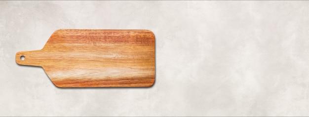 흰색 콘크리트 배경에 고립 된 나무 커팅 보드입니다. 수평 파노라마 배너