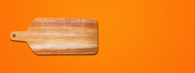 Wooden cutting board isolated on orange background. horizontal banner