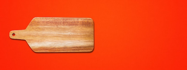 Wooden cutting board isolated on red background. horizontal banner