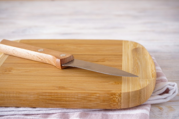 Wooden cutting board on a kitchen towel and a knife on a wooden background.