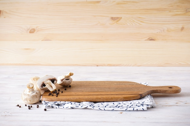 Wooden cutting board and kitchen towel on a wooden background, space for text