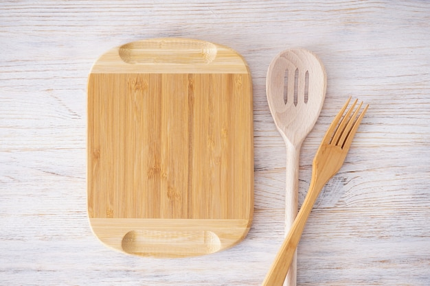 Wooden cutting board and kitchenware on wooden background, place for text. top view.