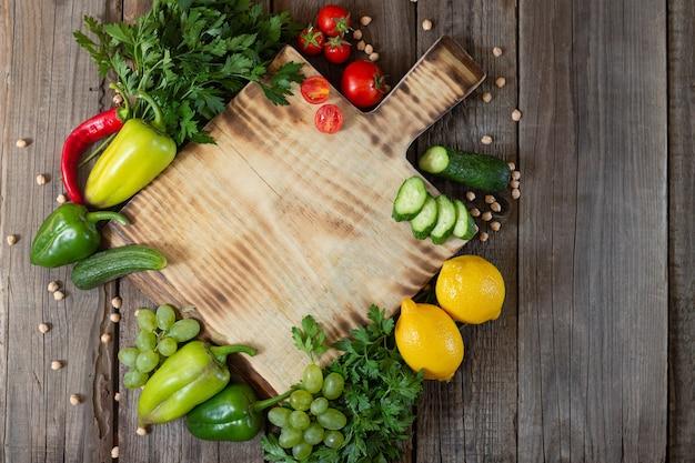 Деревянная разделочная доска рядом со свежими травами, сырыми овощами и фруктами на деревенском деревянном столе