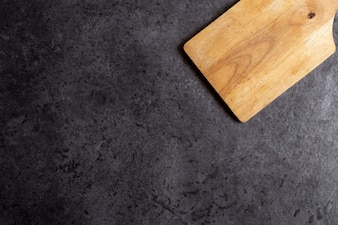 Wooden cutting board on black table background.