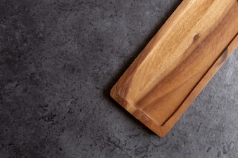 Wooden cutting board on black table background
