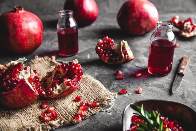 Деревянная разделочная доска на сером фоне с гранатом, здоровой пищей, фруктами