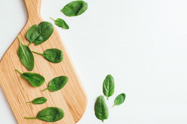 Деревянная разделочная доска на белом фоне с листьями свежего зеленого салата из шпината. концепция здорового питания