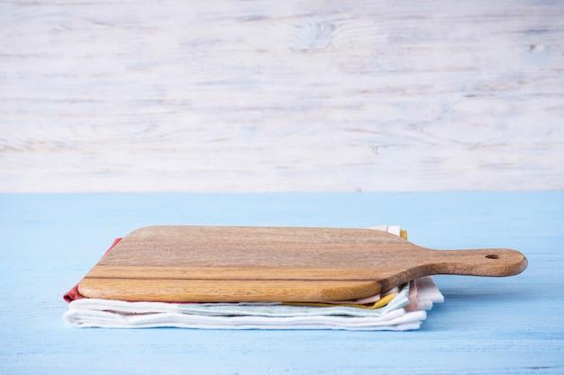 Деревянная разделочная доска на деревянном столе, место для текста.