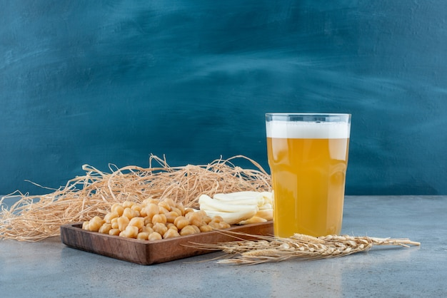 A wooden cutting board of peas and cheese with glass of beer. high quality photo