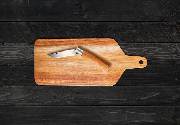 Wooden cutting board and pocket knife on black wood table background