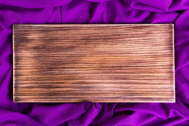 Wooden cutting board on purple, violet napkin cloth.