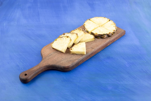 A wooden cutting board sliced pineapple on blue surface