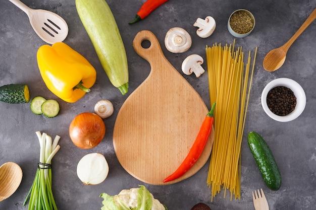 木製のまな板、灰色の背景にスパイスやさまざまな野菜、テキストの場所。上面図。