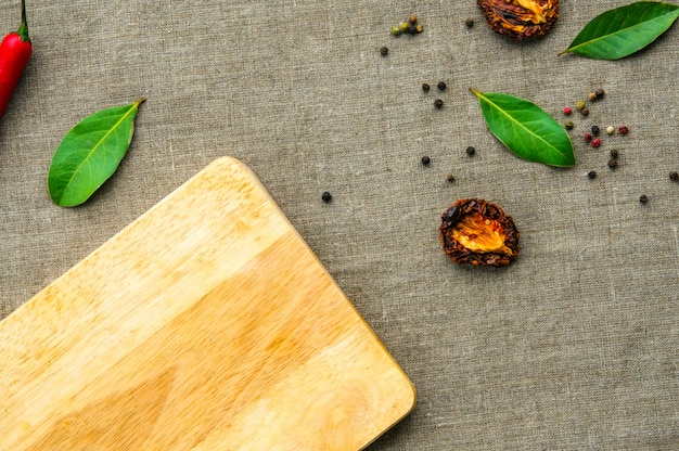 Wooden cutting board and spices on linen fabic as a blank template food