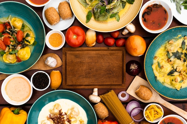 Wooden cutting board surrounded by pasta dishes and ingredient on table