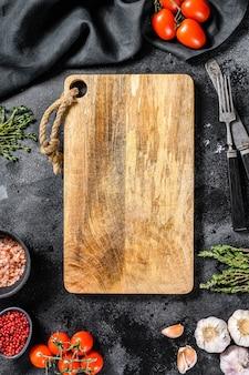 Деревянная разделочная доска в окружении овощей и специй